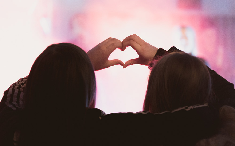 To ungdommer holder hendene sammen i hjerte-form