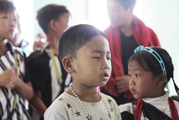 Liten gutt i stjernet hvit t-skjorte står med lukkede øyne foran flere barn