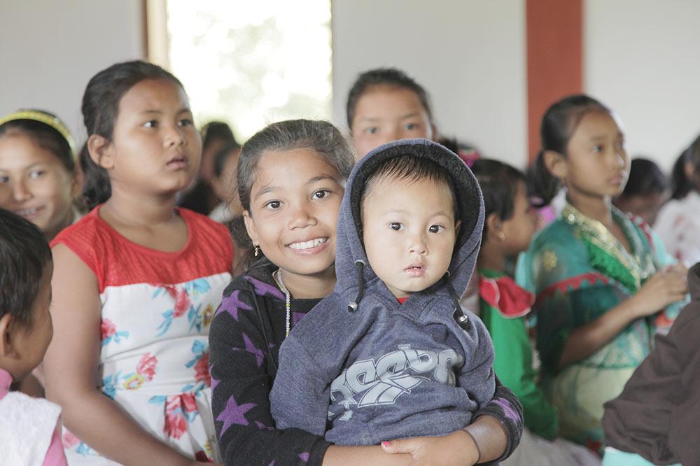 Lite barn på fanget til en smilende, ung jente med flere barn i bakgrunnen