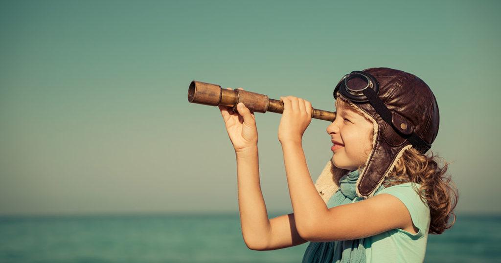 Muntert barn ser gjennom kikkert med hav og blå himmel i bakgrunn