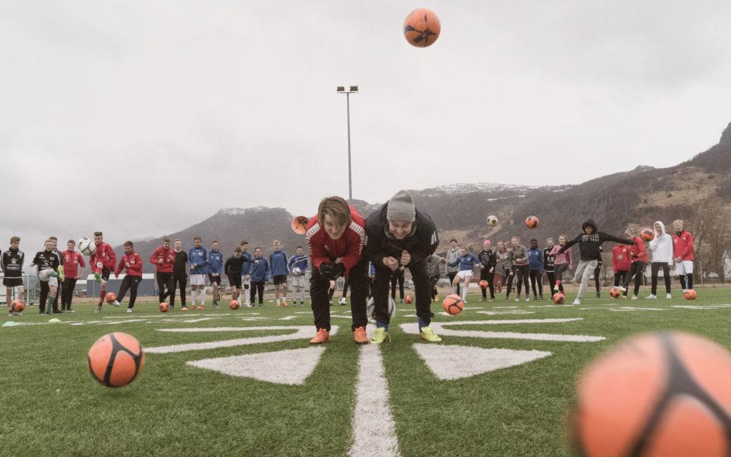 To ledere bøyer seg ned på en fotballbane mens 30 ungdommer forsøker å sparke fotballer på dem