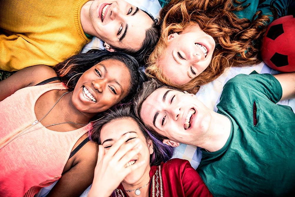 Fem lattermilde ungdommer ligger med hodene i en sirkel