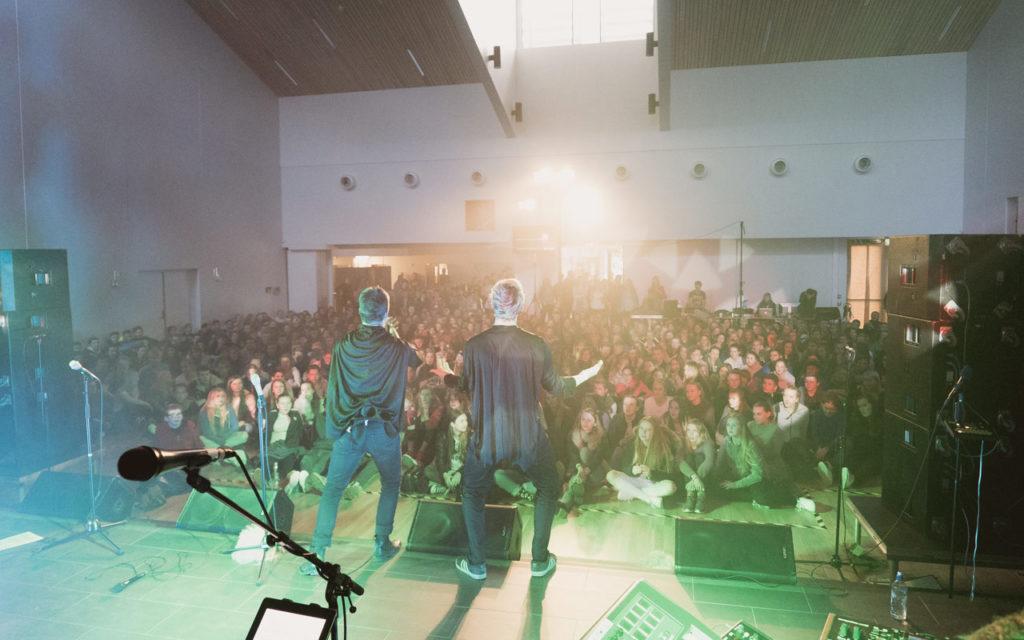 Bilde fra konsertscene ut mot folkemengde, med to artister i forgrunnen