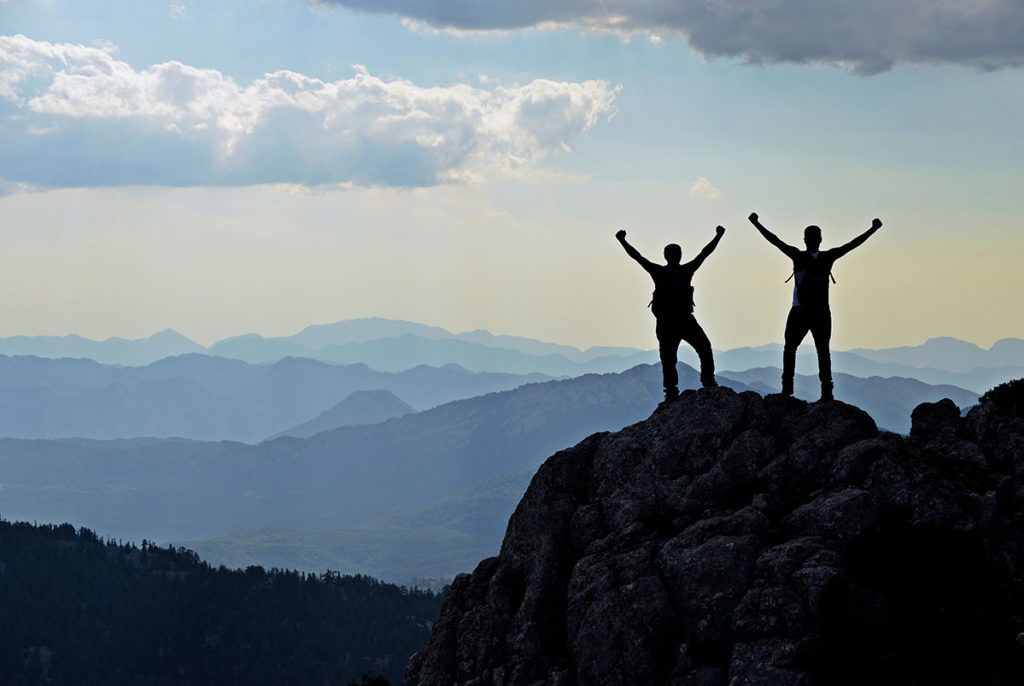 To turgåere løfter hendene og feirer et besteget fjell