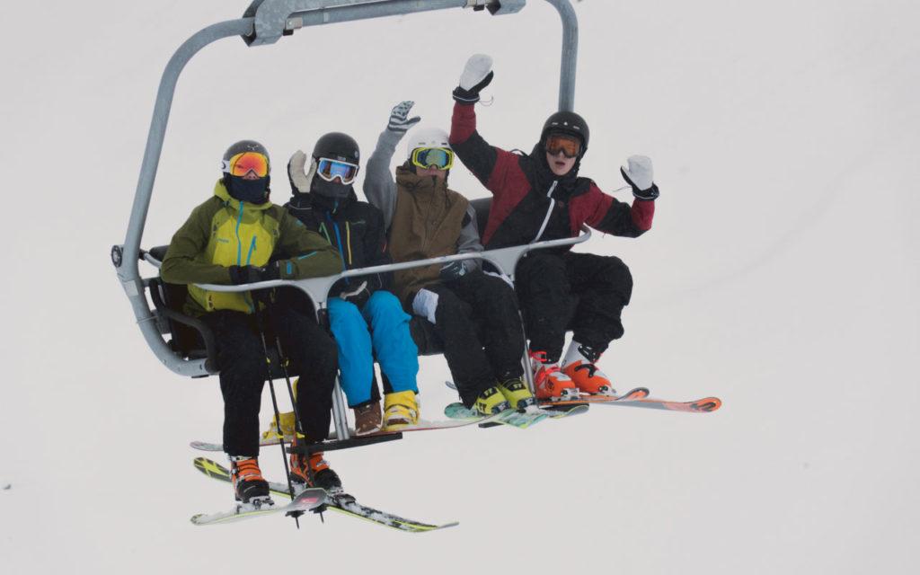 Ungdommer i skiheis vinker til kameraet