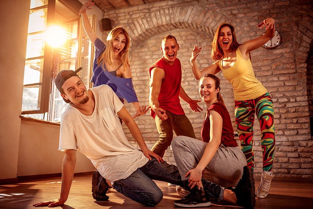 Moderne dansegruppe med ungdommer poserer i gammel bygning, mens solen skinner gjennom ruten