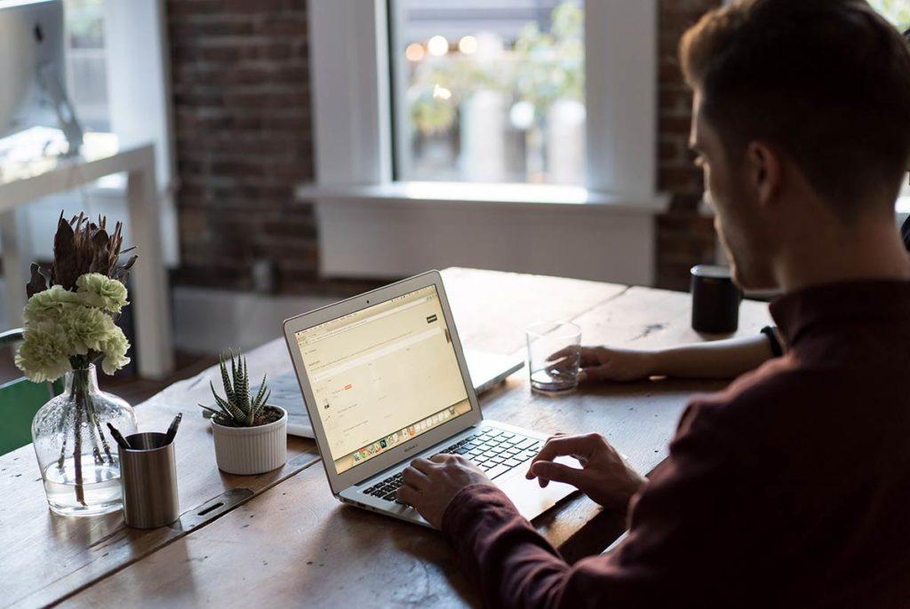 Mann sitter ved et trebord og jobber på en MacBook