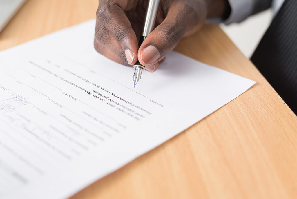 Mann signerer dokument