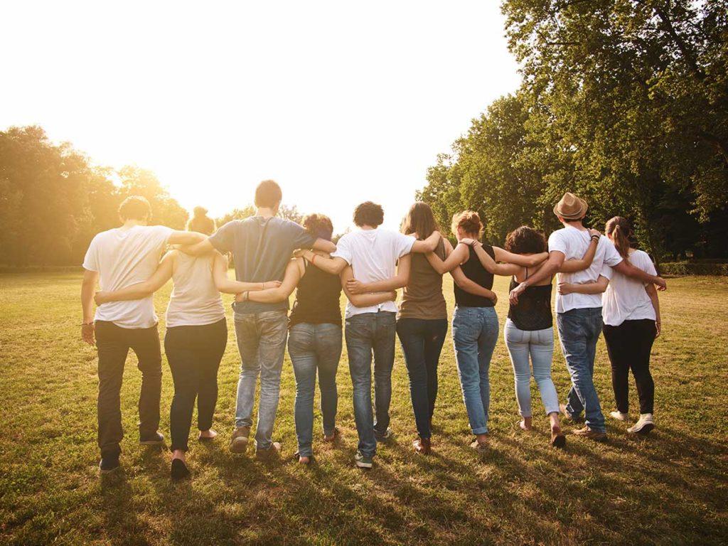 En gruppe ungdommer går bortover gresslette med hendene rundt hverandre