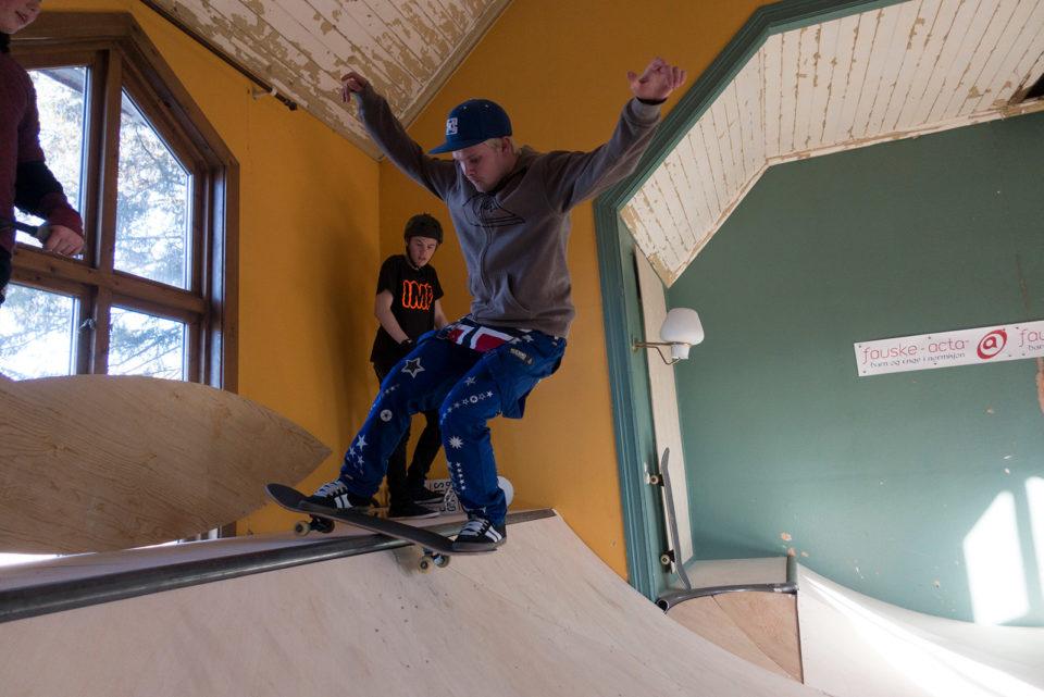 Blåruss skater på en innendørs rampe i et bedehus