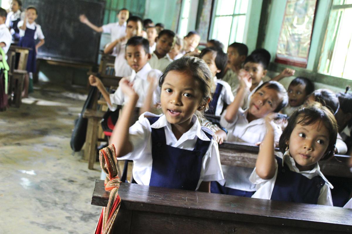 Barn løfter hendene i et klasserom.